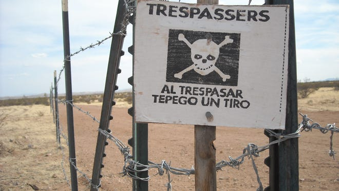"This posted sign hanging on a barbed wire fence is a stern warning for trespassers. Translation reads: ""If you trepspass - you will be shot at."