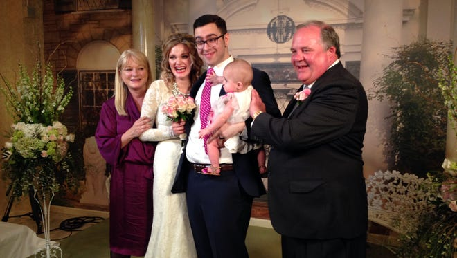 In this April 23, 2015 file photo, newlyweds Kaycee Satava, second from left and Cameron Baker, second from right, with their 6-month-old daughter Lucy, pose for wedding photos with Satava's parents Joyce and Rick inside Elvis Presley's Graceland Wedding Chapel in Las Vegas. The couple's wedding was the first for the chapel. The Elvis Presley exhibit that opened with great fanfare last year has abruptly closed amid a leasing dispute that involves hundreds of the King's artifacts. The Westgate Las Vegas Resort and Casino said it's holding the valuables from its Elvis attraction because the operators, Exhibit A Circle LLC, have defaulted in its 10-year contract with the off-Strip property.
