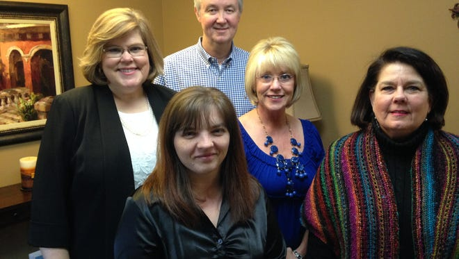 Nancy Choate (left, second row) founded The Law Office of Nancy L. Choate P.C. She is pictured with her husband Curtis, office manager, Christy Vaughn (front left) Kim McAdams and Susan Banks.