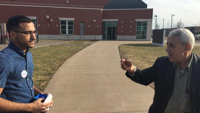 Shiab Mussad, 22, on left, a Bernie Sanders supporter, speaks with Ahmad Musaad, 76, Hillary Clinton supporter, outside Salina School precinct in Dearborn on March 8, 2016