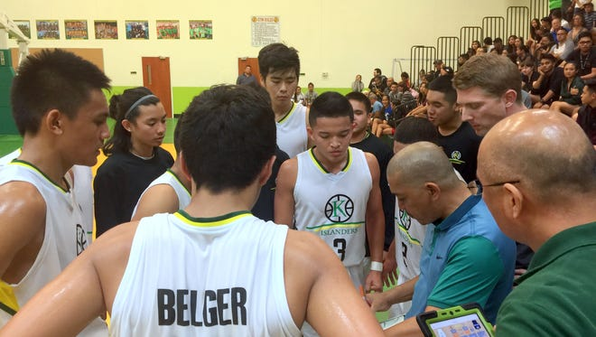The JFK Islanders' surround head coach Rey Serafico during a timeout before the team's 64-58 overtime victory over the Okkodo Bulldogs. The win gives the Islanders a chance to defend their IIAAG boys' basketball league championship.