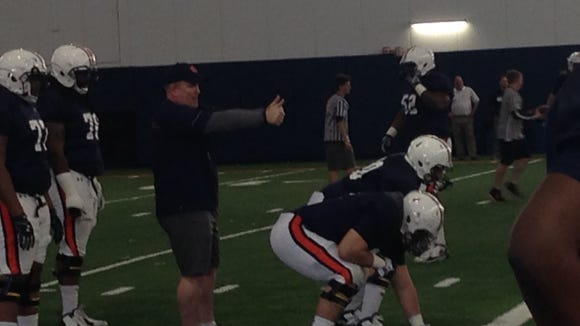 Auburn offensive line coach Herb Hand leading his lineman in a individual position drill on March 8.