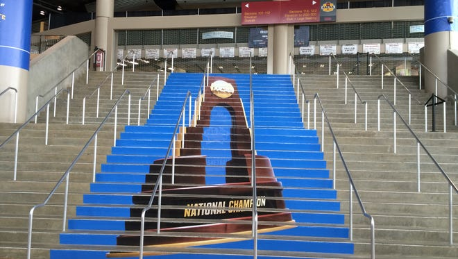 An image of the NCAA Men's Basketball trophy runs up the south staircase at Wells Fargo Arena.