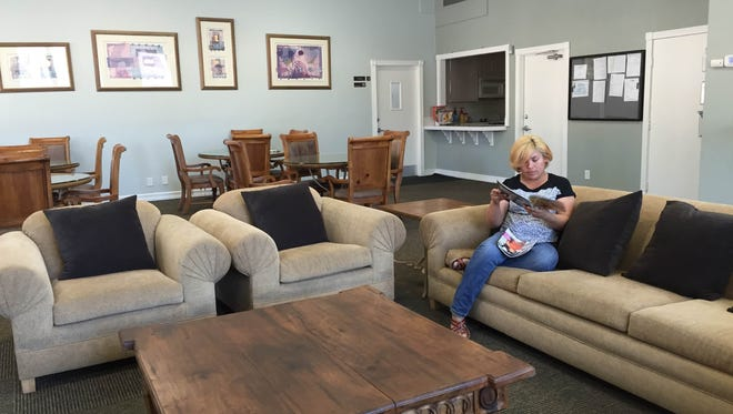 Leticia Valencia reads a magazine while waiting to talk to a property manager in the office and lounge area at Summer Field Apartments.
