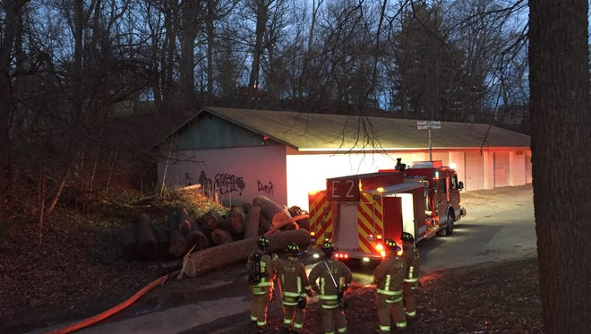 Lancaster firefighters wait to relieve another engine crew putting out a grass fire behind a maintenance building Thursday evening in the northeast corner of Rising Park.