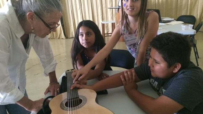Students at the Marquee Academy of Performing Arts learn about the guitar. The Marquee Academy and OperaArts will host an open house on Wednesday, March 30, 2016.