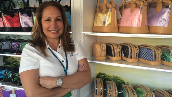 Dominie Brazzel, designer and founder of Dominie Luxury handbags, stands amid her booth at ANA Inspiration at Mission Hills Country Club in Rancho Mirage in 2016.
