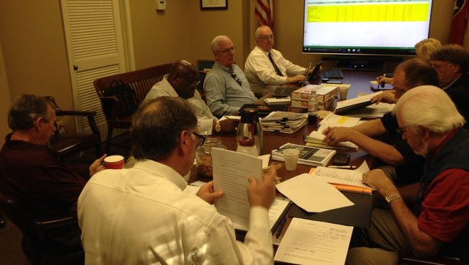 Members of the Jail Project Screening Committee review architectural firms Monday.