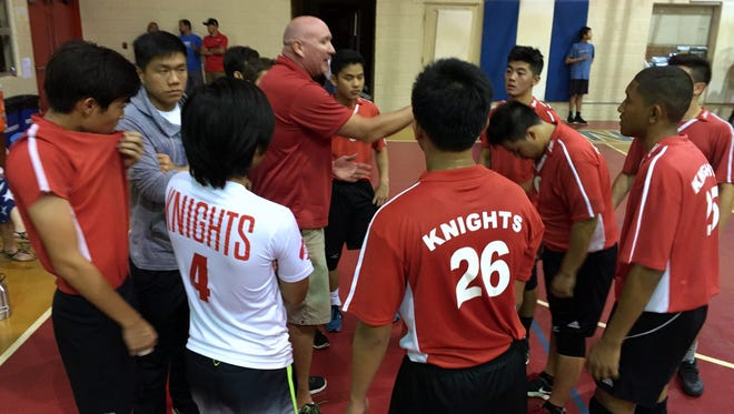 St. John's Knights' head coach Chris Shepherd talks to his team during a time out. The Knights defeated the Friars at home in IIAAG high school boys volleyball league action on Friday, April 8.