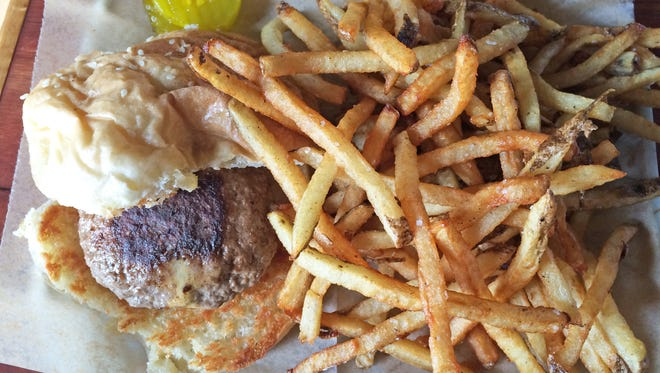 A cow and pig burger and an order of fries at The Bar'ber Shop Tavern on Thursday, April 7, 2016.