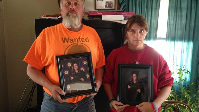 Scott Root and Michelle Root hold college graduate photos of their daughter Sarah, 21. Sarah Root was in a fatal accident the day after her commencement ceremony.