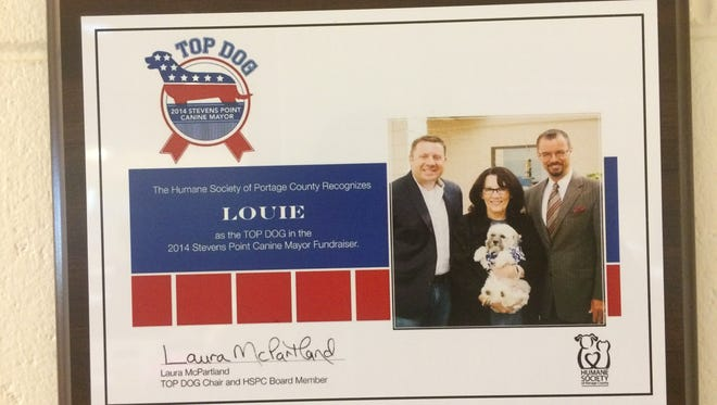 A plaque showing the winner of the 2014 Stevens Point Canine Mayor Competition, Louie, hangs at the Humane Society of Portage County.