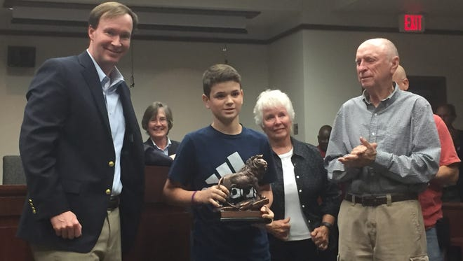 The Solicitor's Office honored Michael Wagner, 12, for his courage in testifying against the man who killed his mother. Pictured from left: Solicitor Walt Wilkins, Wagner, and his grandparents, Frank and Vera Davis.