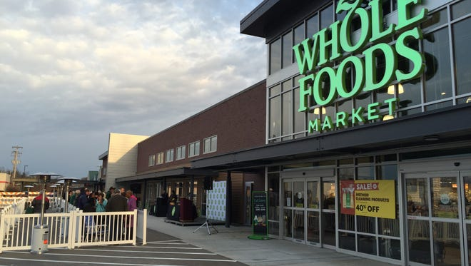 Dozens of people line up outside Whole Foods Market in Meridian Township for its grand opening Wednesday morning.