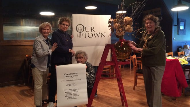 Members of the Countryside Garden Club's flower show committee (standing from left) Charlotte Erbland of Millville, Barbara Ann Logan of Millville, Paula Carman of Pittsgrove and (seated) Jo Pagano of Vineland plan the entrance to the club's annual flower show, to be held April 15 to 17 at Cumberland County College in Vineland.