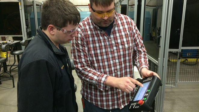 High school student Nathan Brown, 16, looks on as Fox Valley Technical College Instructor Ben Cebery walks him through operation of a robotic welding machine on April 12.
