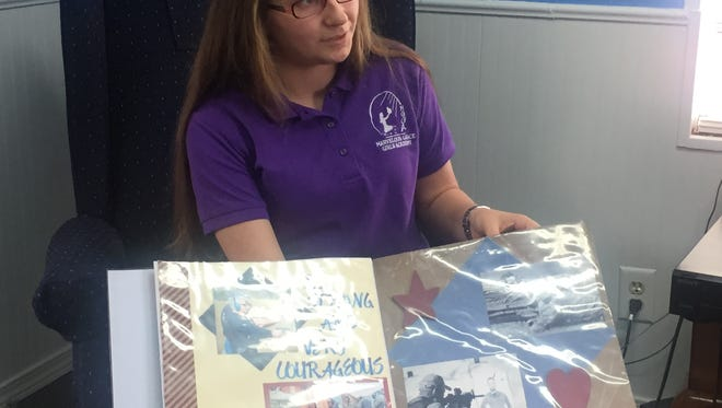 Lilliy Scarbrough shows off a scrapbook commemorating the courage of law enforcement officers and military personnel.