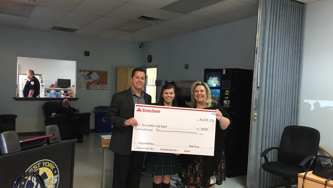 State Farm agent Vincent Cerceo, left, awards sophomore Lexi Zambito and Heather Hoffman, director of admissions for York Catholic's seat belt usage percentage during the fifth annual York/Adams High School Seat Belt Challenge.
