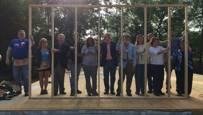Volunteers perform a ceremonial raising of the wall of Nakita Bouie's new Habitat home Thursday in Simpsonville.