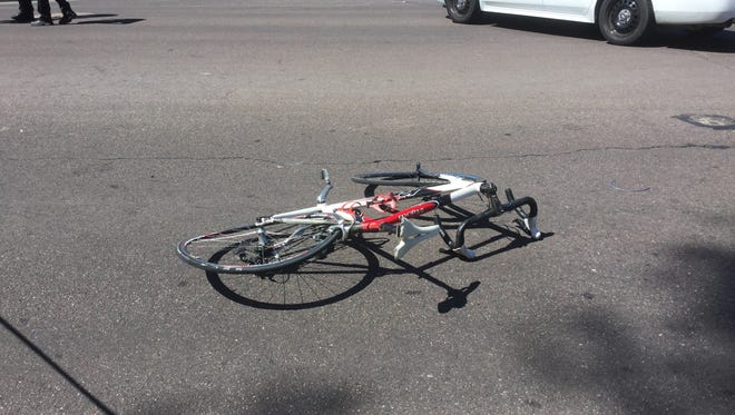 A collision involving a motorcycle and a bicycle sent two people to the hospital and temporarily closed Shea Boulevard on Sunday afternoon.