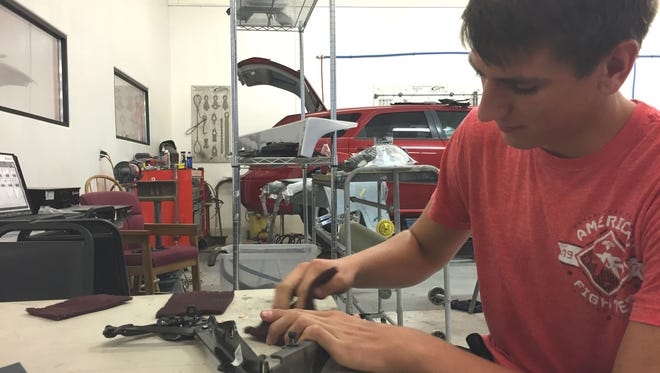 Junior Reid Jensen worked on car parts at ACT after getting the job with help from the Hire a Bulldog program. Jensen usually runs around the shop, but he broke his foot two hours before prom on Saturday.