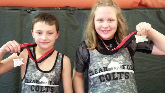 Maddie Rhees and her twin brother Maddox show off the medals they won at the Ohio Novice state tournament. Maddie finished second wrestling against boys.