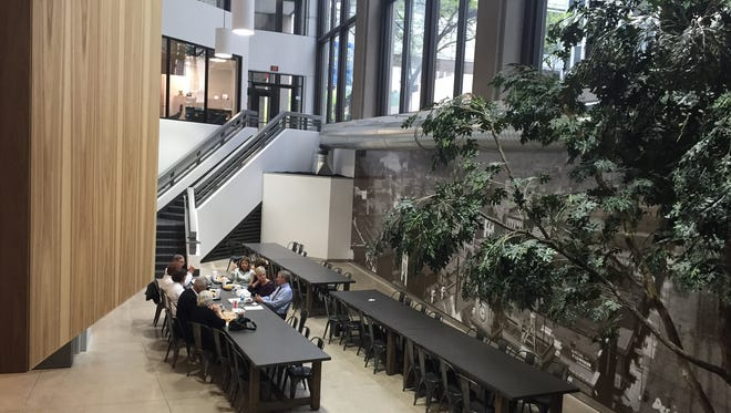 The new Local Bites food court features communal tables and two trees. Guests access the restaurants by walking down one of two staircases.