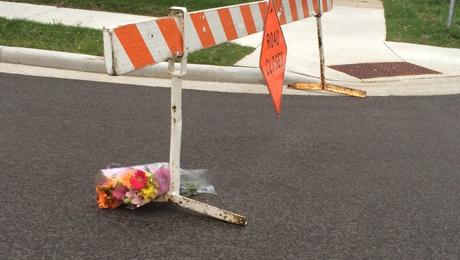 A bouquet of flowers rests on a barricade Thursday morning near the home where police say a man shot himself and his two children early Wednesday.