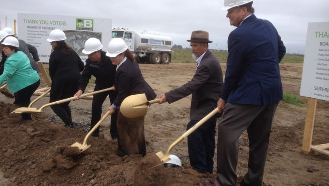 Architect Peter Kasavan, right; and school board trustee Philip Tabera, to his left, toss their ceremonial shovels of dirt at Friday's groundbreaking.
