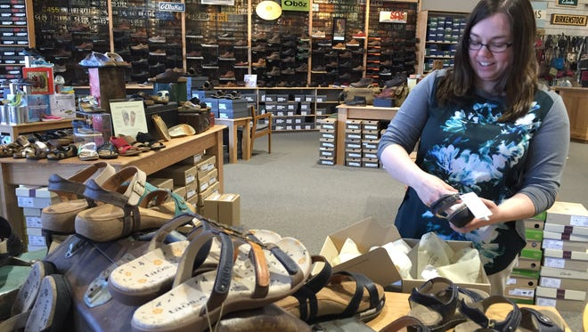 Angela Hixson arranges shoes in Brown's Shoe Fit Co.'s new space at The Square, 3500 S. College Ave., Fort Collins.