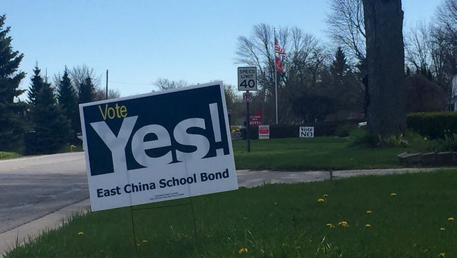 "A ""Vote Yes!"" sign about the East China School District bond is posted in a yard just south of Marine City Tuesday, May 3, 2016, with a sign supporting votes against the bond issue in the distance."
