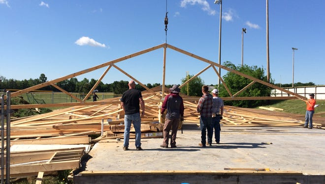 Eagleville parents work on removing the framework for the baseball and softball programs'  new indoor facility. It collapsed Wednesday due to high winds.