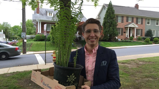 Brenton Grom holds the plant he bought after attending the Wilmington Flower Market for the first time.