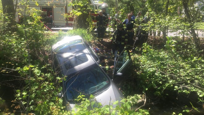 Firefighters at a car that plunged into the shallow Sheldrake River along Pinebrook Boulevard in New Rochelle, May 8, 2016. The driver, an older woman, was said to be fine but was transported to White Plains Hospital to be checked out.