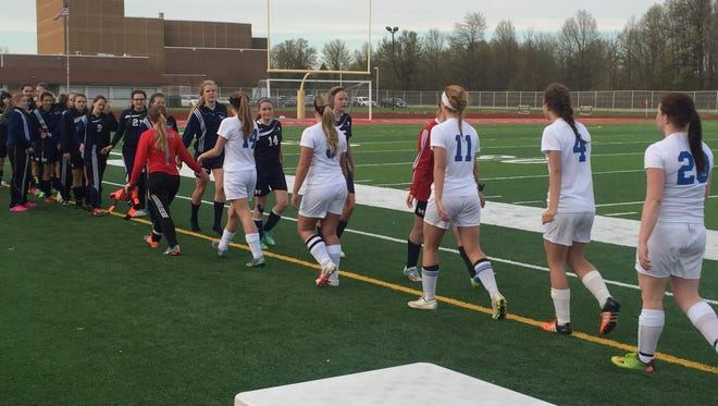 The St. Clair and Marysville soccer teams shake hands after St. Clair's 7-0 victory at East China Stadium