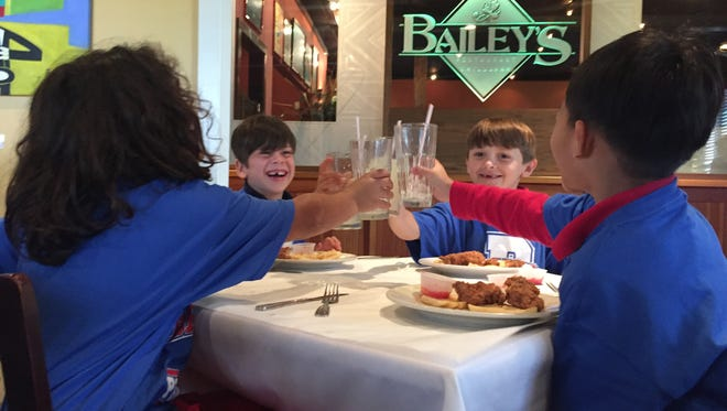 Clockwise from left: Second graders Amir Balbeisi, Beckett Buxton, Jackson Tolbert and William Nguyen toast during a special lunch held in their honor at Bailey's Seafood & Grill. The Broadmoor Elementary students were treated by the restaurant owner for earning straight As this school year.