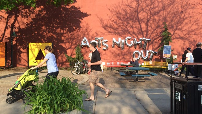 A family strolls by Turner Park in Old Town during Friday's Arts Night Out. The kickoff is the first of eight evening events planned this year.