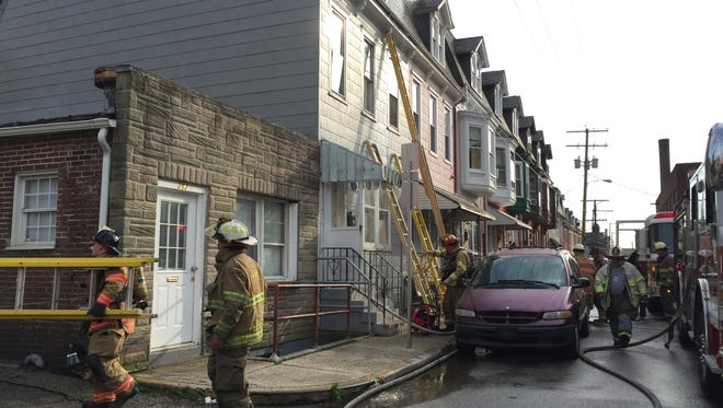 Firefighters contain a third-floor fire on East Poplar Street in York on Tuesday evening.