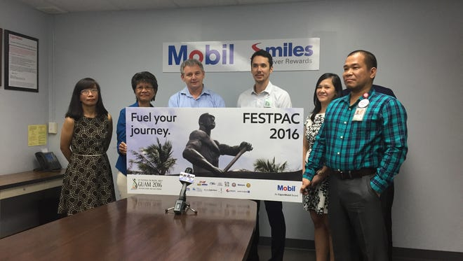 Mobil Oil Guam Inc. President Charles Ewart, center, along with Festival of Pacific Arts Organizing Committee Chairman Nate Denight and other Mobil officials talk about the company's $20,000 fuel donation for the festival at its Hagåtña office on May 12.