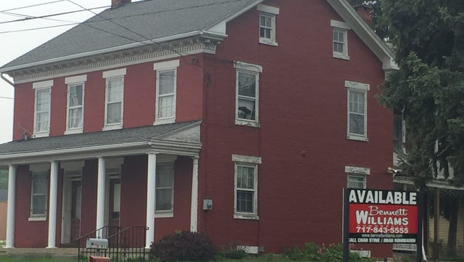 This house, built in 1861, according to a sign posted on its exterior, will be one of two buildings destroyed to make way for retail space.