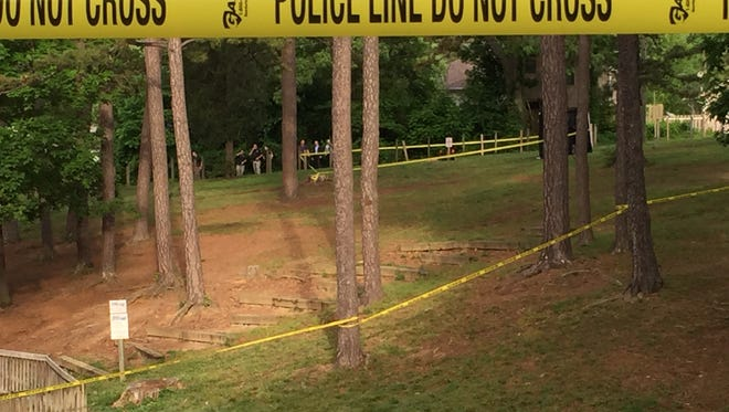 Asheville police officers investigate a deceased body found at the park near Ira B Jones Elementary school.
