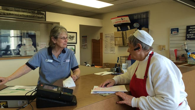 Dianne Zirbel assists Lucille Kirkegaard, owner of the Yum Yum Tree, at the Baileys Harbor post office.