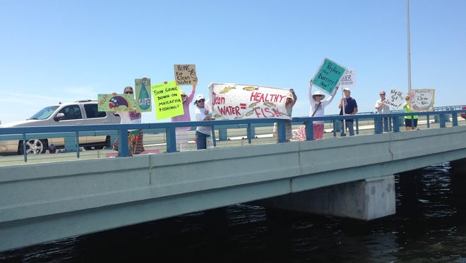 """A handful of residents from Matlacha, Bokeelia, St. James City and Fort Myers took up a spot on the Matlacha Bridge on Sunday to raise awareness for issues linked to water quality. Those who took part in the peaceful protest that started around noon swished signs, yelled slogans and offered information on why water quality was important. Gabriele Solterra, of St. James City, was adamant that the estuary that is part of Matlacha Pass be kept clean. """"It really helps us all to have clean water. That's what the estuary is for,"""" she said."""