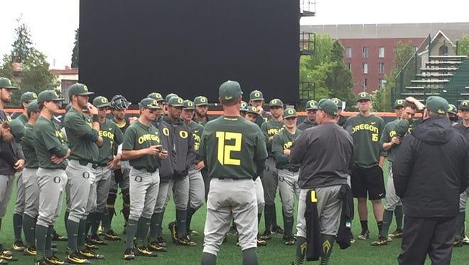Oregon coaches and players gather after the Ducks clinched the Civil War series with a 6-3 victory Sunday at Goss Stadium in Corvallis.