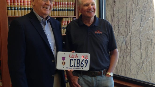 Utah Rep. Lowry Snow, Dist. 74, left, and St. George resident Arnold Breitenbach pose with Breitenbach's new license plate Thursday at Snow's office. Breitenbach, a Vietnam veteran, battled against motor vehicle policy banning the number 69 on license plates in an attempt to honor his military service and the year he was wounded in combat. Snow spearheaded legislation this year that exempted veterans from the rule.