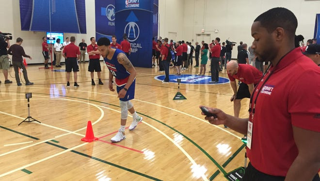 Jasper Bibbs, right, times Denzel Valentine in an agility drill at the NBA Combine earlier this month in Chicago. While Valentine awaits the NBA draft, Bibbs is hoping for an NBA career, too, as a strength and conditioning coach. Bibbs and Valentine have known each other since Valentine was in middle school.