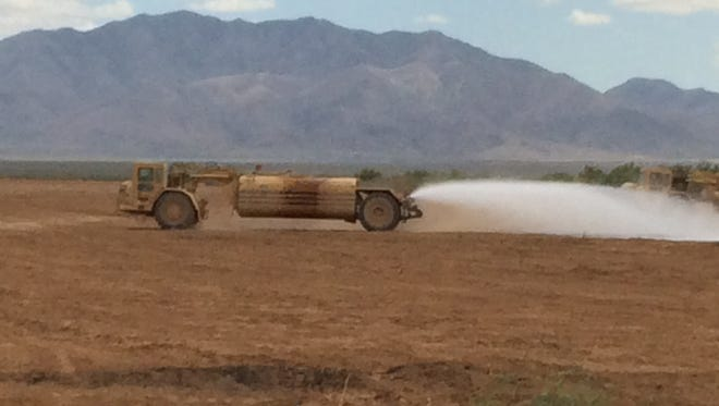 A truck applies Gorilla-Snot to an area of land that has been creating blowing dust.
