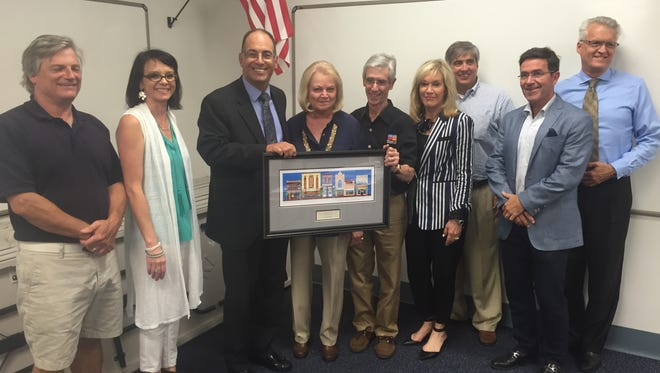 Bill Dollarhide, center right, accepts a congratularoty plaque from the Downtown Improvement Board Tuesday night.