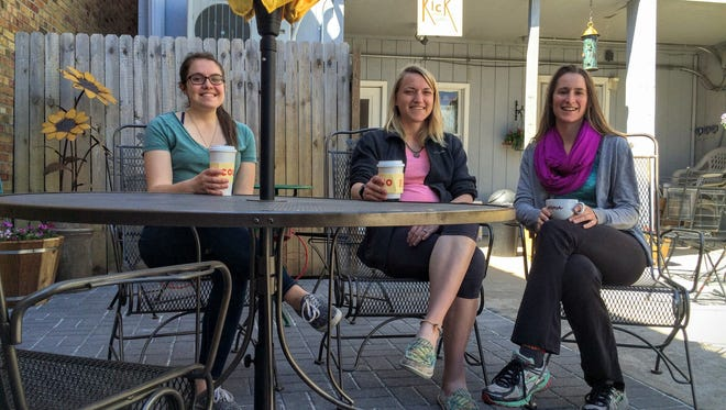 Baristas Becca Malcore, left, and Laura Ingrouille with Kick Coffee owner Liz Butler, center, enjoying coffee in the newly renovated Kick Back Garden in the rear of the Third Avenue coffee shop.