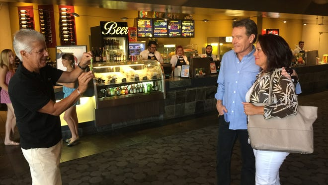 Emmy Award-winning actor Bryan Cranston lets Ralph Piscitelli of Palm Desert take a photograph of him with Piscitelli's wife, Carol, in the lobby of Cinemas Palme d'Or. Cranston is a part owner of the theater, where he has long been unusually accessible to its patrons.